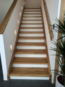 Treppe aus Eichenholz mit weißen Setzstufen und Geländer mit Edelstahlseilsystem