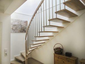 Treppe mit Trittstufen aus Eichenholz, weißer Zahnwange und Edelstahlsprossen