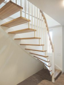 Treppe aus Buchenholz mit weiß lackierten Geländersprossen