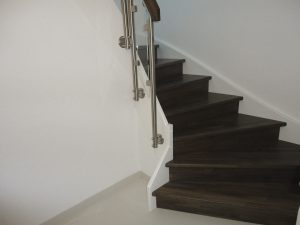 Treppe mit gebeizten Tritt- und Setzstufen, weiß lackierten Wangen und seitlich aufgesetztem Glasgeländer