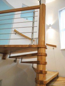 Spindeltreppe aus Eichenholz mit Wandhandlauf und abschließenden Geländer mit Edelstahlgurten