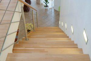 Stufenbelege aus Buchenholz mit Geländer aus Edelstahlgurten und rundem Buchenholzhandlauf