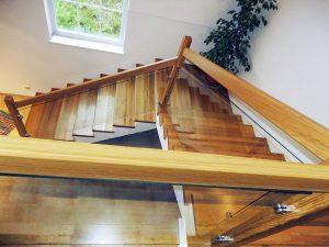 Stufenverkleidung mit Glasgeländer und Holzhandlauf